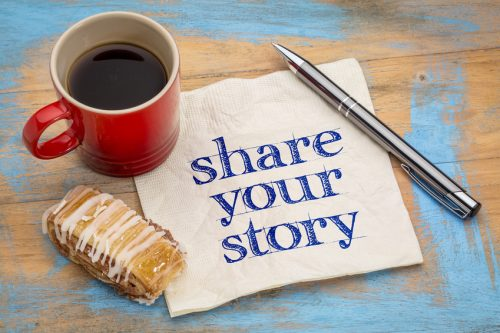 share your story- handwriting on a napkin with a cup of espresso coffee and cookie against grunge painted wood